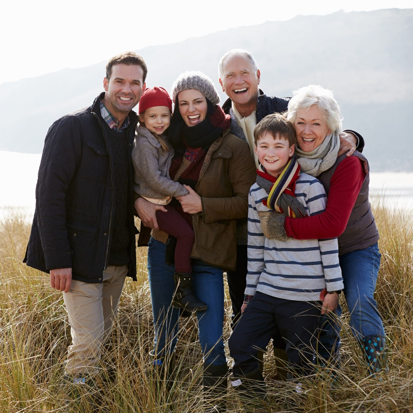 Multi Generation Family In Sand Dunes On Winter Beach Smiling To Camera